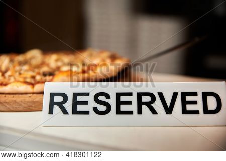 Plastic Plaque With The Inscription Reserved On The Restaurant Table Against The Background Of The P