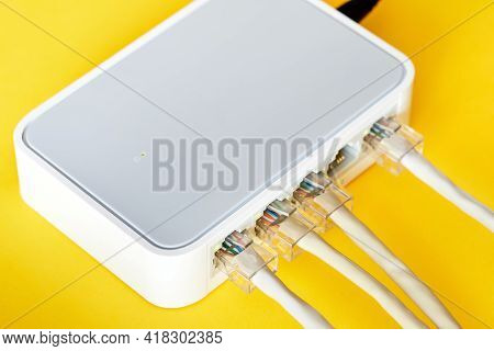 Ethernet Cables Connected To Desktop Switch Or Routerboard On A Yellow Background. Close-up, Selecti