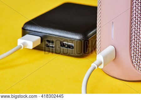 Power Bank Charges Portable Audio Speaker Using A Usb Cable On A Yellow Background. Close-up, Select
