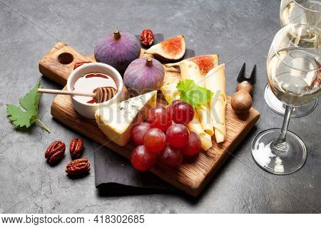 Antipasto plate with cheese, figs and grapes. Appetizer board and white wine