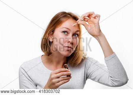 Portrait Of A Young Woman Smearing Medicine On A Pimple On Her Forehead. White Background. Acne And