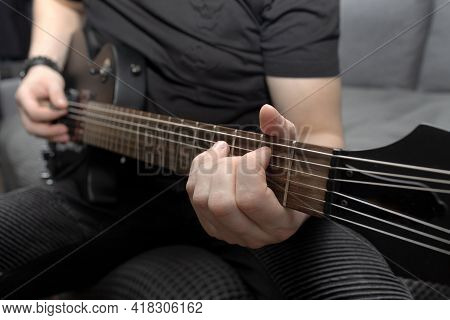 Musician Playing Black Electric Guitar. Guitar Fretboard Close-up. Learning To Play The Guitar. Self