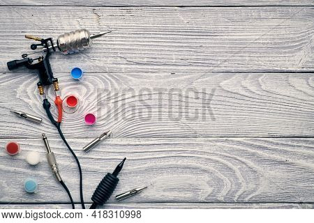 Tattoo machine, tools and supplies over wooden background. Tattoo studio.