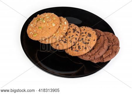 Cookies Of Cocoa Dough, Chocolate Chip Cookies And Cookies Sprinkled With Different Seeds On Black D