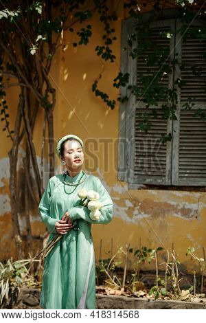 Atractive Young Asian Woman In Traditional Dress Standing Outdoors, Closing Eyes And Enjoying Summer