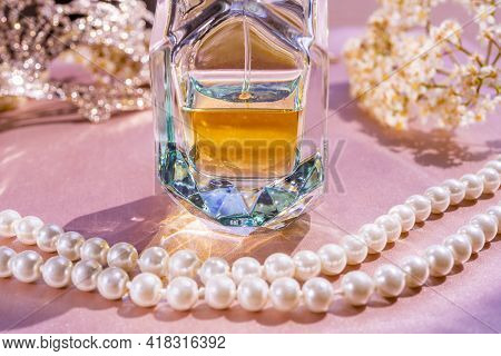Luxury Perfume In Beautiful Bottle With White Pearls Necklace And Accessory On Toilette Table. Selec
