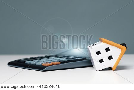 Mortgage Calculator Or Real Estate Business Concept. Office Desk With A Bend Over House And Calculat