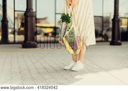 Girl Holding Mesh Shopping Bag And Cotton Shopper With Vegetables Without Plastic Bags, Wooden Backg