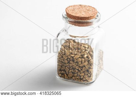 Glass Jar With Pieces Of Gold On White Background