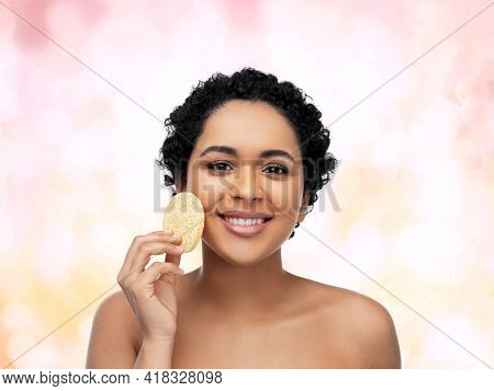 beauty, people and skincare concept - young african american woman with bare shoulders cleaning face with exfoliating sponge over pink lights background