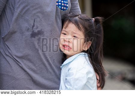 Adorable Asian Girl Is Crying With Tears On Her Cheeks. Child Rested On Her Mother's Belly. Children