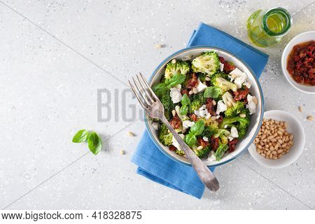 healthy broccoli salad with feta cheese sun dried tomatoes pine nuts.. vegetarian low carb keto diet