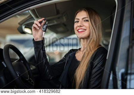 Young happy woman showing the key of her new car in a car dealer saloon