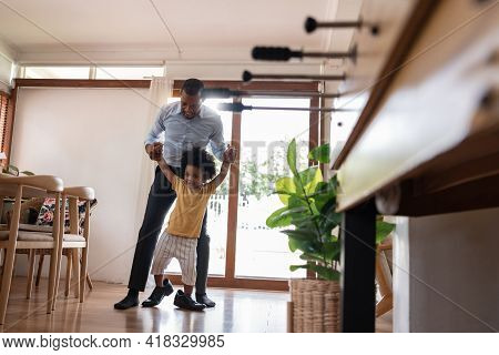 Happy Smiling African Dad Holding Hands And Helping Little Adorable Child Stepping With His Shoe At