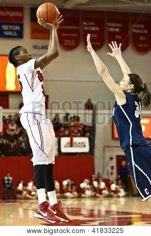 JAMAICA-FEB 2: St. John's Red Storm guard Shenneika Smith (35) shoots over Connecticut Huskies guard Kelly Faris (34) at Carnesecca Arena on February 2, 2013 in Jamaica, Queens, New York.