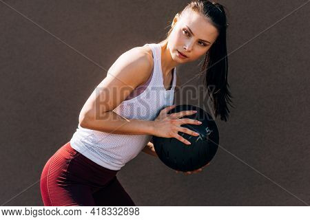 Sporty Young Woman Doing Exercises With A Medicine Ball Outdoors On A Sunny Day. Fitness Female Exer