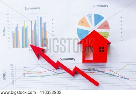 The Red Wooden House Is Placed On The Graph Or Business Information. Business Growth Concept. Econom