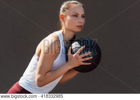 Portrait Of A Sporty Young Woman Doing Exercises With A Medicine Ball Outdoors On A Sunny Day. Fitne