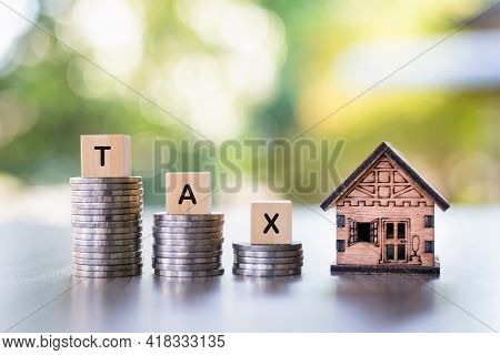 A Model House, The Word Tax Is Placed On Top Of The Coin Pile. House Tax. Housing Tax.