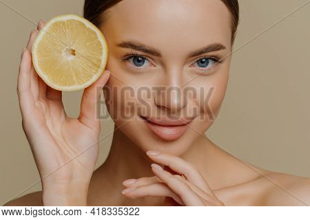 Beauty Portrait Of Healthy Young Topless Brunette Woman Touches Chin Gently Holds Half Of Juicy Fres
