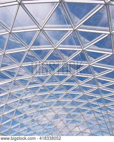 Glass roof of modern building windows. Metal grid blue sky pattern.