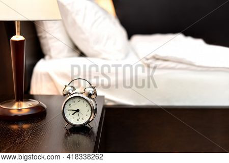 Alarm Clock Next To Bed In Bedroom Without People. Made Bed Early In Morning In Hotel Room Or At Hom
