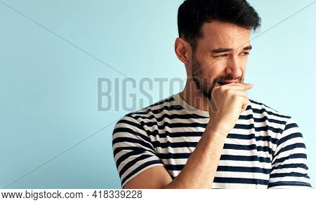 Horizontal Portrait Of A Worried Young Man Looking At On Side And Bite His Fits, Isolated On Light B