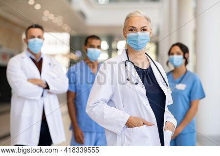 Portrait of smiling woman doctor looking at camera and standing in hospital with team in background wearing protective face mask during covid-19 pandemic. Healthcare workers team during corona virus.