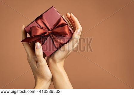Woman holding brown gift box isolated on brown background. Close up of female hands holding elegant present with copy space. Young woman hands carrying beautiful gift box with satin ribbon.