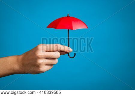 Female hand with small red umbrella isolated on blue background. Close up of woman hand holding mini umbrella against blue wall with copy space. Insurance, protection and security concept.