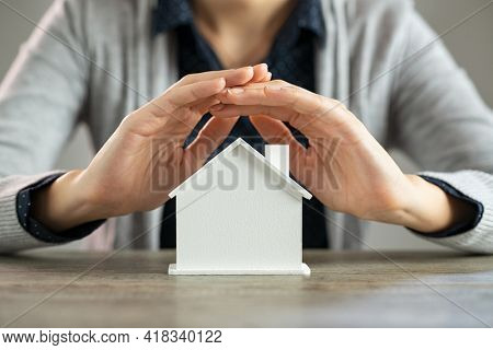 Close up of young woman hands protecting a model of house on table. Detail of woman holding hands over cardboard figure of house at desk. Woman protecting her real estate investment on scale model.