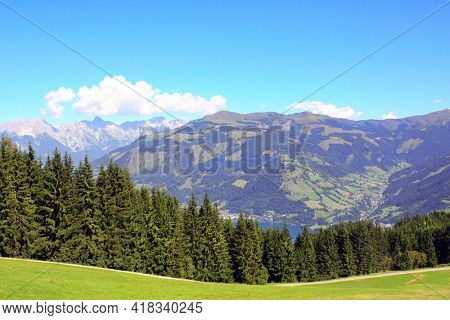 Alps mountains in Tirol, Austria. Aerial view of idyllic mountain scenery in Alps with green grass and fur-trees on sunny day. European mountain landscape in National park High Tauern (Hohe Tauern)
