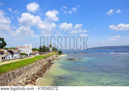 Famous lighthouse and palm trees in Galle Fort. Indian Ocean, sunny day, Sri Lanka