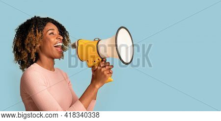 Announcement Concept. Cheerful Black Woman Shouting With Megaphone In Hands, Blue Background