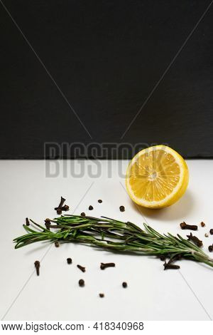 Lemons With Cloves And Fresh Rosemary On White And Black Background. Place For Text.