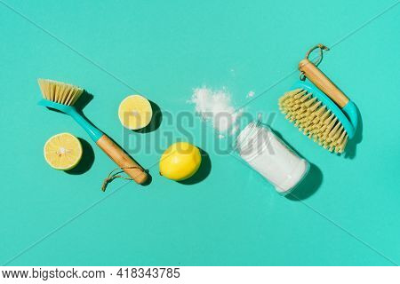Baking Soda, Lemon, Mustard Powder And Bamboo Brushes Against Household Chemicals Products Over Blue