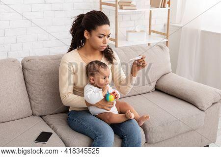 Black Mom Measuring Temperature For Sick Baby Having Fever Indoor