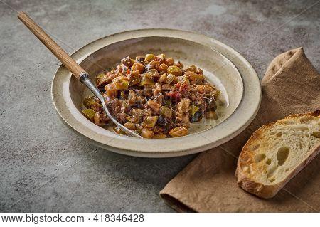 Homemade Traditional Sicilian Caponata With Eggplant, Zucchini, Tomatoes, Olives And Ciabatta Bread.