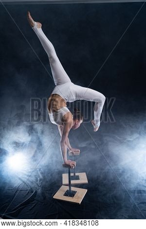 Flexible Circus Artist - Female Acrobat Doing Handstand On The Back And Smoker Background. Concept O