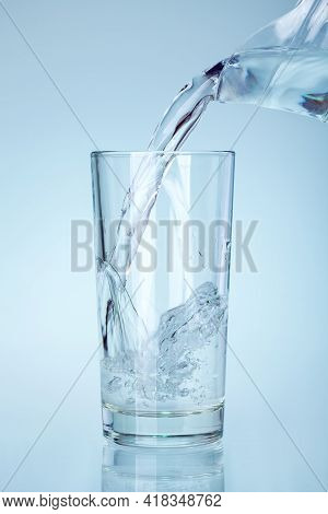 The Clear Glass Is Filled With Water From The Spout Of The Glass Jug A Stream Of Water With Splashes