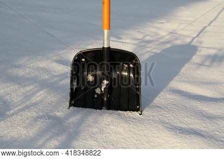 On A Sunny, Frosty Morning, A Shovel With An Orange Handle For Snow On A White Background Sticks Out