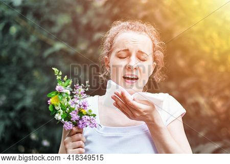 Young Woman Sneezing With Bouquet Of Flowers. Concept: Seasonal Allergy.