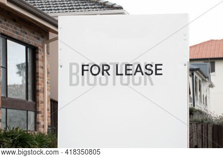 For Lease And Sign On A White Display Outside Of A Residential Building. Renting Concept