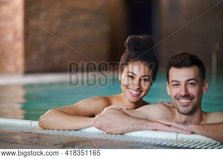 Portrait Of Young Couple In Swimming Pool, Looking At Camera.