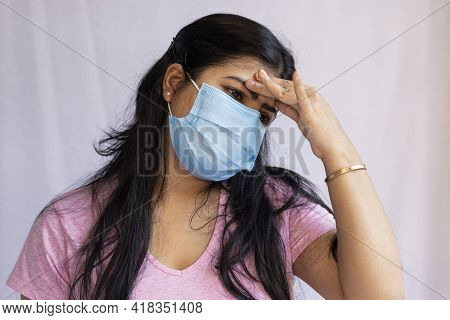 A Mid Adult Indian Asian Woman Wearing Surgical Nose Mask And Touching Forehead For Headache, Health