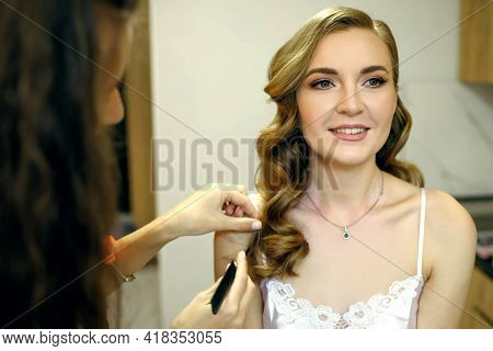The Hairdresser Makes A Beautiful Hairstyle For A Young Woman At Home. A Master Stylist Arranges The