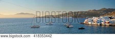 Sunset in Mykonos, Greece, with cruise ship and yachts in the harbor