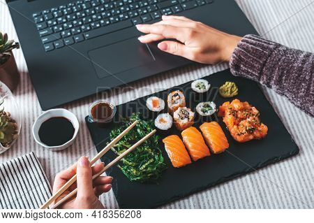 Woman Eating Sushi Takeaway At Work Desk Overhead. Eating Sushi For Lunch Break, Lunch Meal At Work