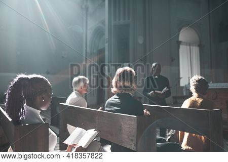 Group Of People Listening To Priest During Sunday Mass In The Church