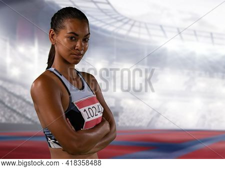Portrait of african american female athlete with arms crossed against sports stadium. sports and fitness concept